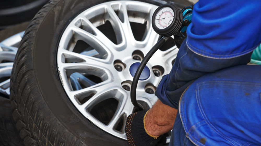 A Norwood Auto Services technician inflates a car tyre